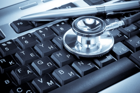 shiny stethoscope and pen on keyboard in blue tint photo