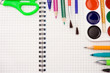 pencils, felt pens, paint brush and scissors on checked paper of notebook photo