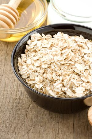 bowl of oatmeal and milk on wood background photo