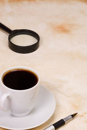 magnifier and cup of coffee at texture Stock Photo - 13946105