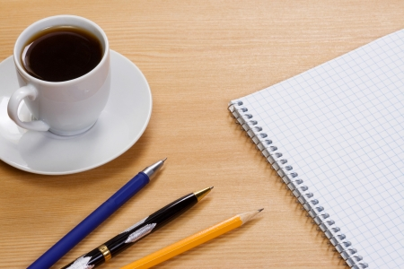 coffee, notepad and pens on table