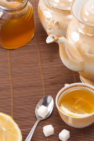 tea, pot and honey on table  photo