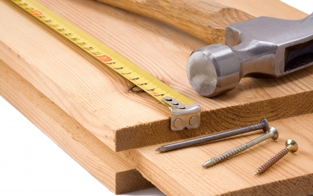 housebuilding: hammer and tape measure on wood brick Stock Photo