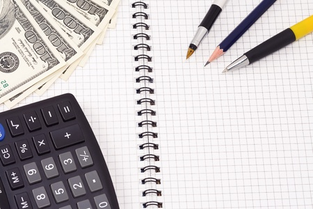 pens, calculator and dollars on pad photo