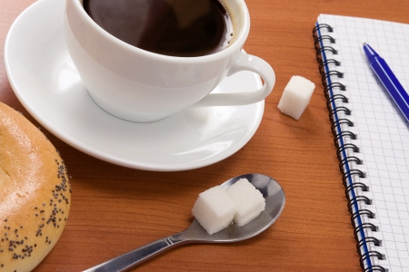 cup of coffee, pad and pen on table Stock Photo - 14021629