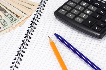 dollars, pens and calculator on pad photo