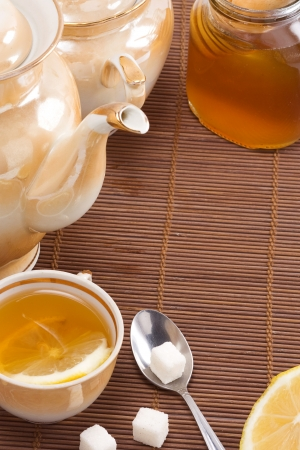 teapot, honey and spoon on wood texture photo