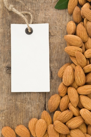nuts almond and tag price label on wood background photo