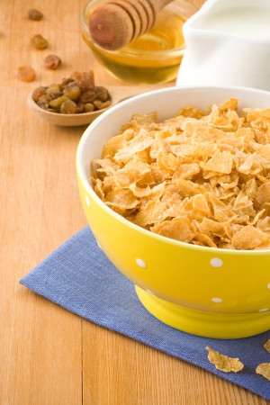 Bowl of corn flakes and milk on wood background photo