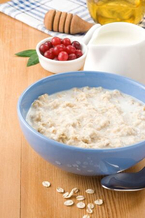 oatmeal with milk and honey on wood background photo