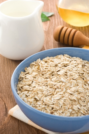 Bowl of oat and milk on wood background photo