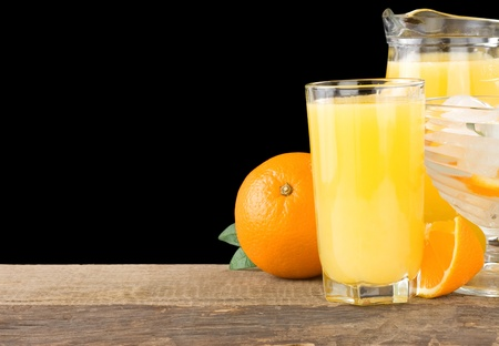 juice and oranges isolated on black background photo