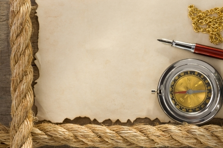ropes and compass on old vintage ancient paper background texture photo