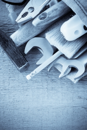 kit of tools and bag on wood background texture photo