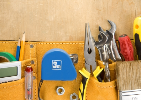 suede belt: tools in construction belt on wooden background texture