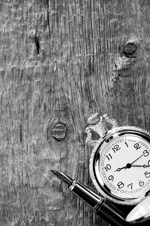 ink pen and watch on wooden background photo