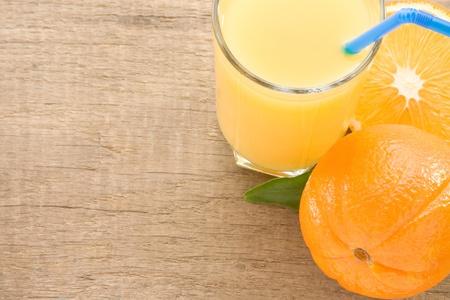 fresh fruits orange juice in glass on wood board background photo