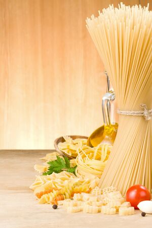 raw pasta and ingredients on wooden background Stock Photo - 14765694