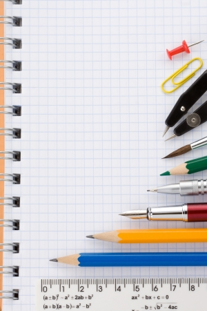 school supplies on checked notebook photo
