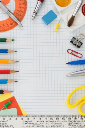 school supplies on  checked notebook paper photo