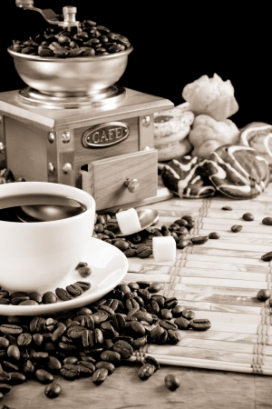 cup full of coffee, beans, pot and grinder in black and white photo