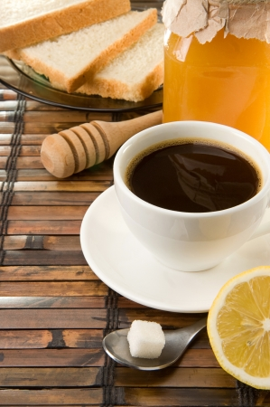 coffee, honey and bread on straw table photo