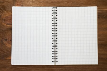 checked notepad  on wood background photo