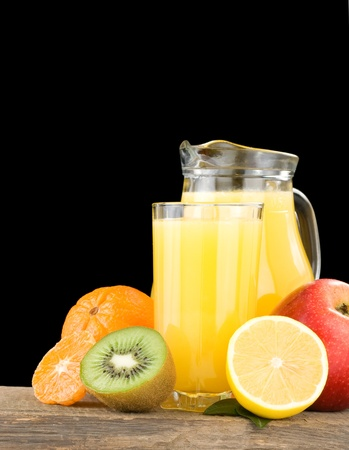 fresh fruits and juice in glass isolated on black background photo