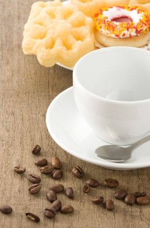 cup with coffee beans at old table photo