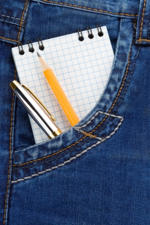 notepad and pencil with pen on jeans packet background photo