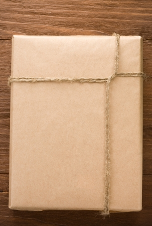 parcel wrapped packaged box on wood background photo