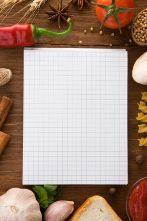 notebook for cooking recipes and spices on wooden table photo