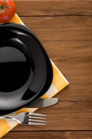 plate, knife and fork at napkin on wooden background Stock Photo - 15585534