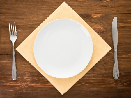 white plate, knife and fork at napkin on wooden background photo