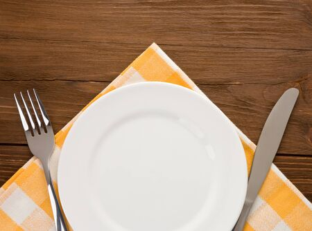 plate, knife and fork at napkin on wooden background Stock Photo - 15585522