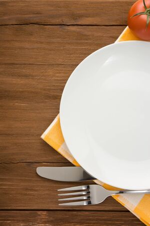 plate, knife and fork at napkin on wooden background Stock Photo - 15585526
