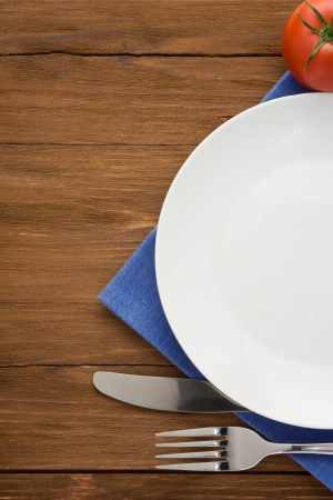 plate, knife and fork at napkin on wooden background Stock Photo - 15585529