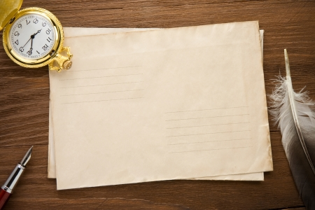 history: watch and ink pen at envelope on vintage wood background texture Stock Photo
