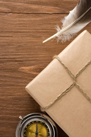 parcel wrapped with brown paper tied with rope on wood background photo