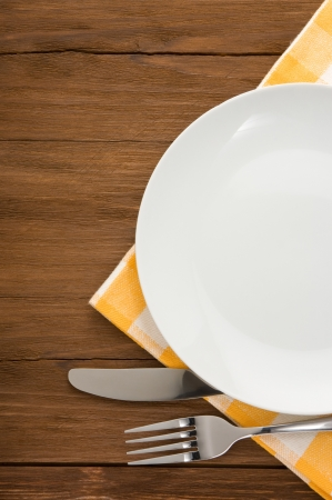 utensil: plate, knife and fork at napkin on wooden background