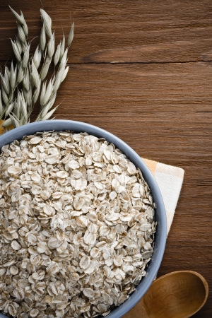 ear checked: oat flakes in bowl on wooden background Stock Photo