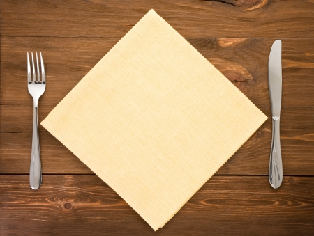 knife and fork at napkin on wooden background photo