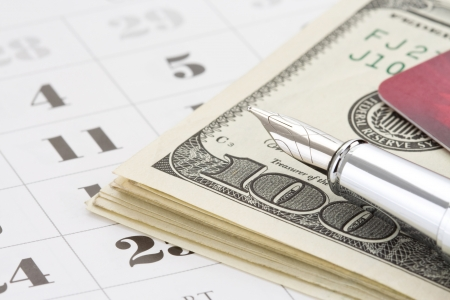 ink pen and dollar money on calendar background photo