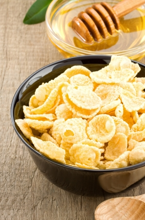 bowl of corn flakes and honey on wooden background photo