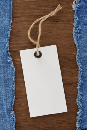 etiquetas de ropa: jean azul y la etiqueta de precio sobre fondo de textura de madera