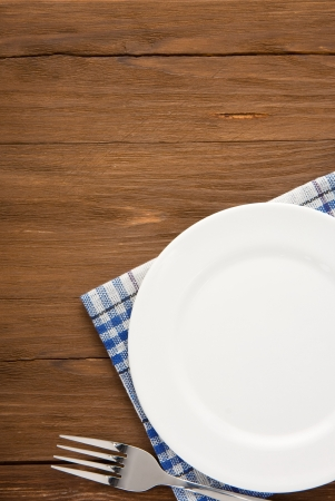 white plate and fork at napkin on wooden background Stock Photo - 16657754