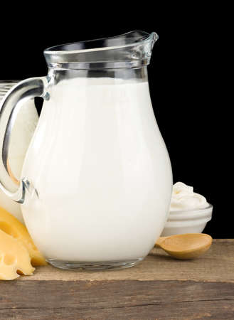 milk products and cheese on wood isolated at black photo