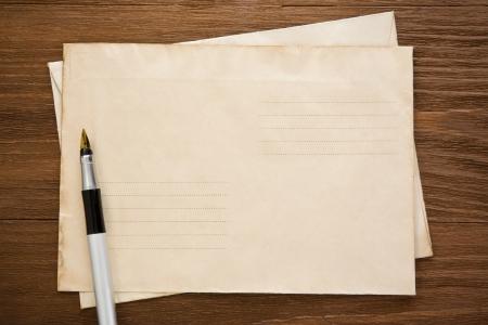 pen en oude postenvelop op houtstructuur
