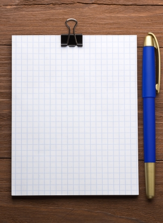 checked notepad and pen on wood background photo
