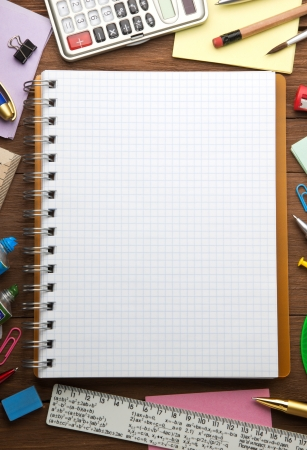 school supplies and checked notebook on wood background photo